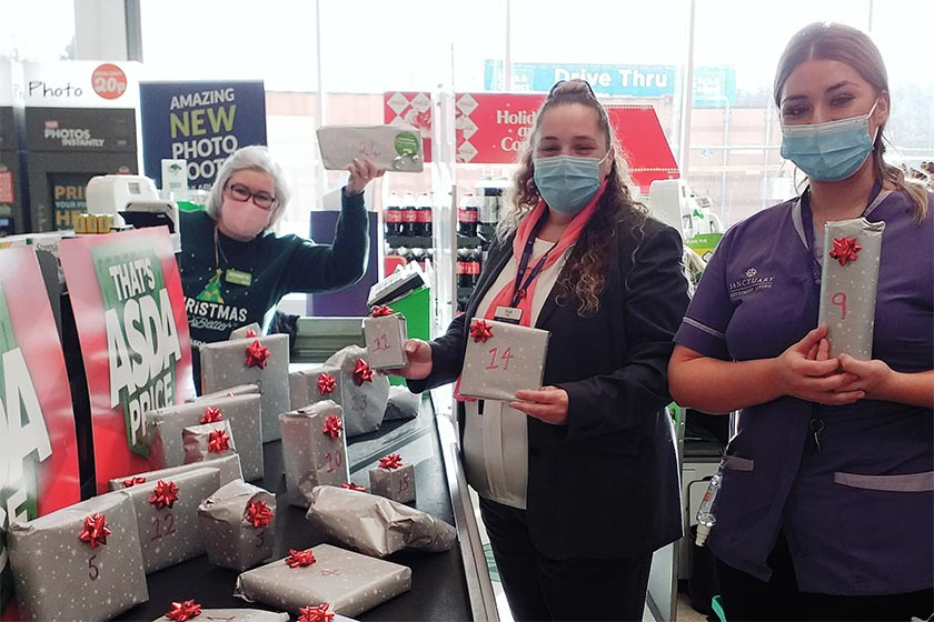 Sanctuary Retirement Living and Asda staff posing with wrapped presents at an Asda checkout