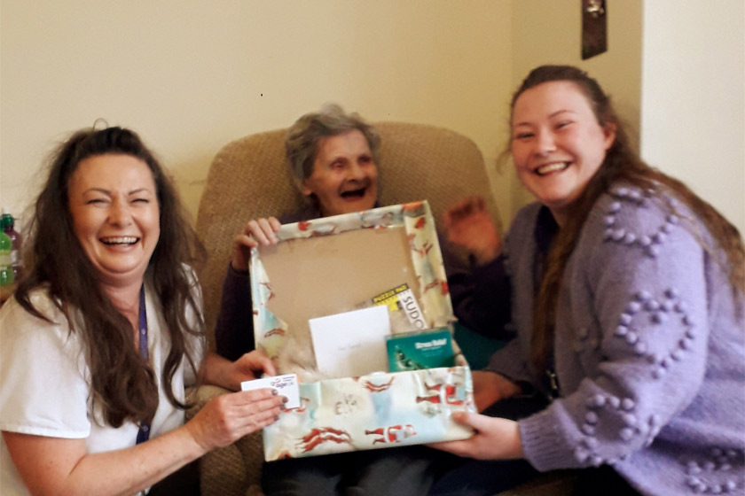 Sanctuary staff and residents celebrate receiving a Secret Santa gift