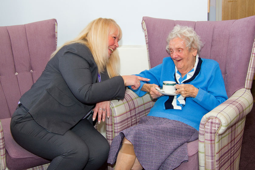 A Sanctuary Retirement Living staff member laughing with a resident at Jubilee Court.