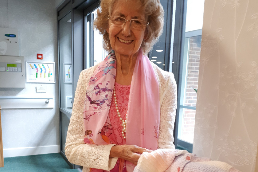 Roman Ridge resident with a hand-knitted baby cardigan