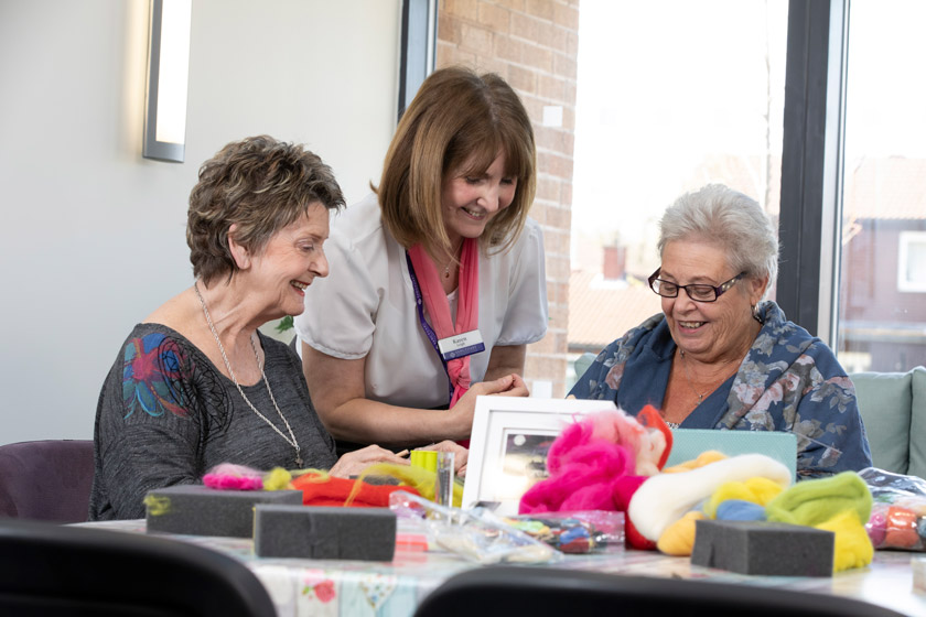 Residents take part in an arts and crafts activity session with the support of Sanctuary Retirement Living staff..