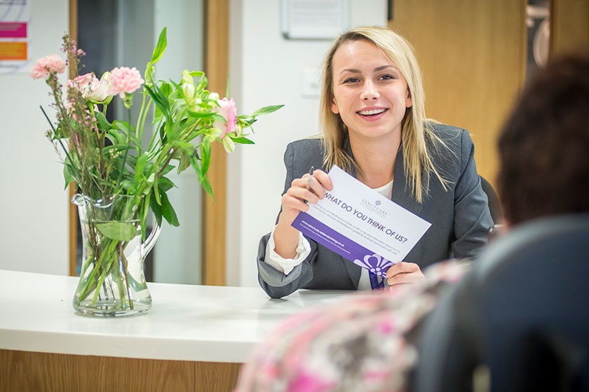 A member of staff holding a feedback card