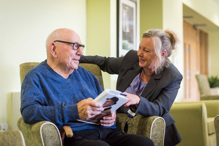 A staff member speaking to a resident in a retirement living property.