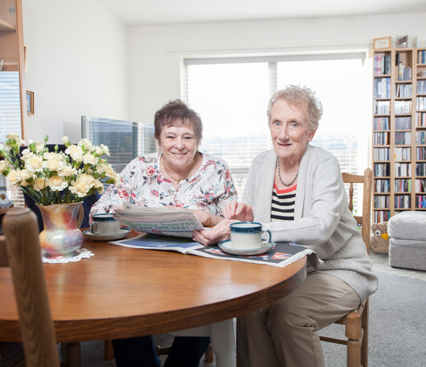 Two residents enjoy a cup of tea and read the newspapers together.