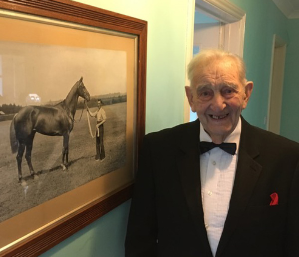 Resident stands beside a picture of his younger self with a horse.