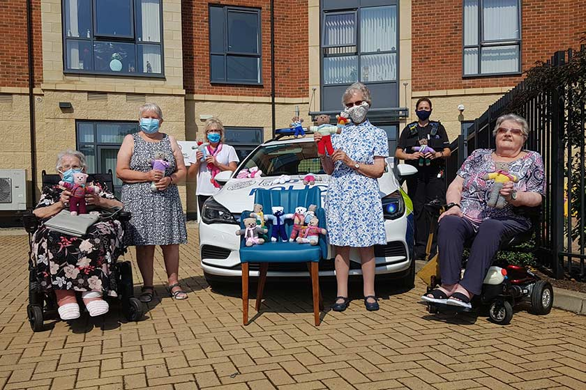 Residents and police officer with the knotted teddies outside of Lawley Bank Court.