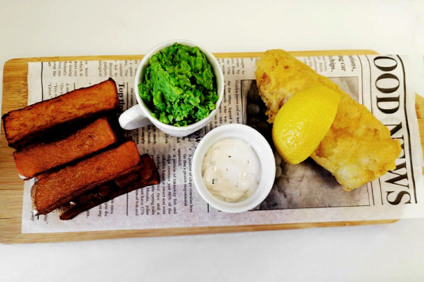 Fish and chips with mushy peas served on a board