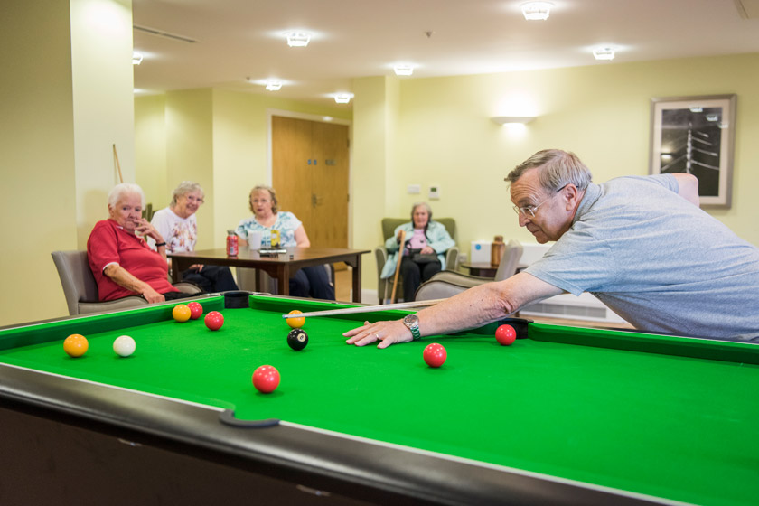 Residents playing pool in a communal area.