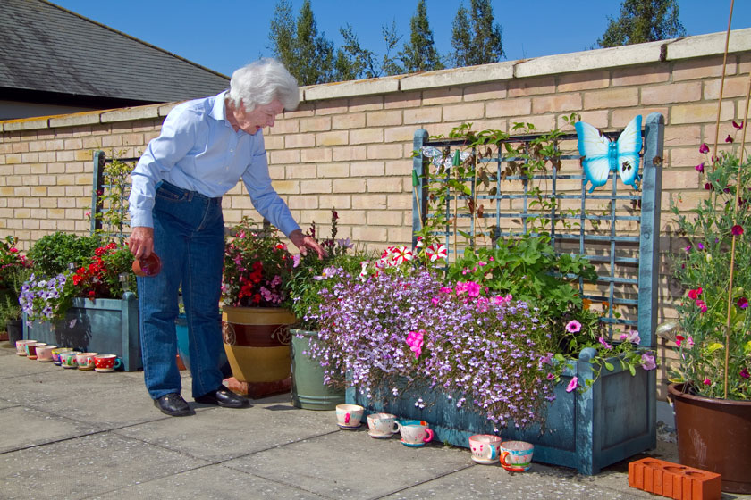 Connie Kendrick admiring flowers at Millbrook House.