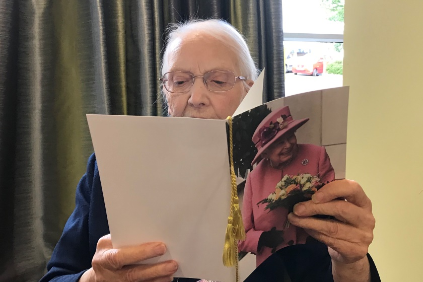 Wimborne House resident, May, opens her 100th birthday card from the Queenfrom