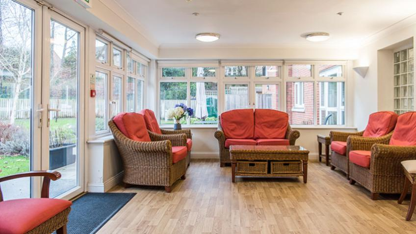 The conservatory overlooks the garden with comfortable seating.