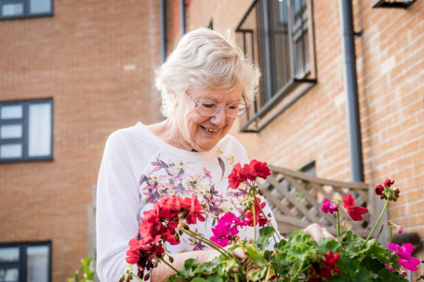 A Sanctuary Retirement Living resident tending flowers in one of our communal gardens.