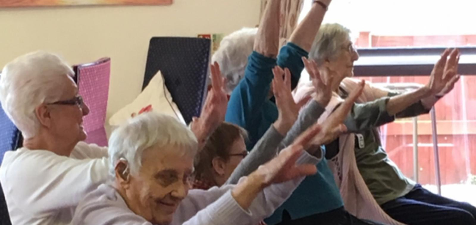 Residents and visitors at Harry Garrett Court enjoy some chair-based exercise.