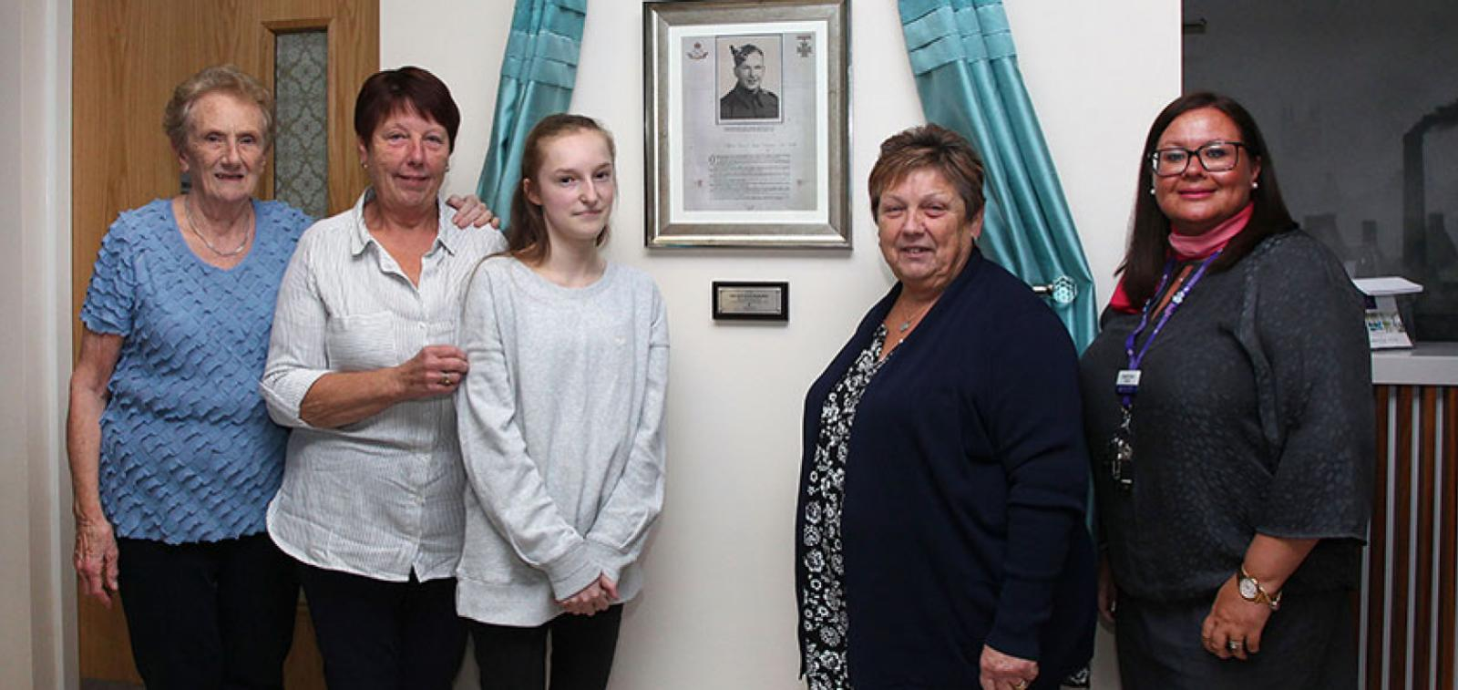 Staff, residents and relatives of Lance Sgt Baskeyfield next to the plaque that was unveiled in his honour.